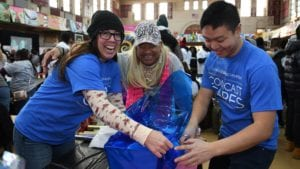 Comcast Cares Day volunteers wrap gifts.