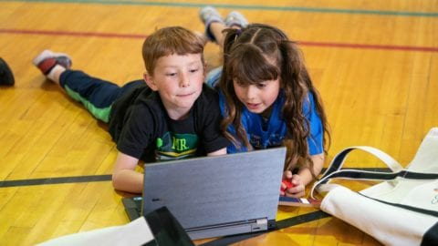 Children from the Tutt Boys & Girls Club of the Pikes Peak Region lay on the floor and use a laptop together.