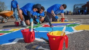Comcast Cares Day volunteers paint a playground.