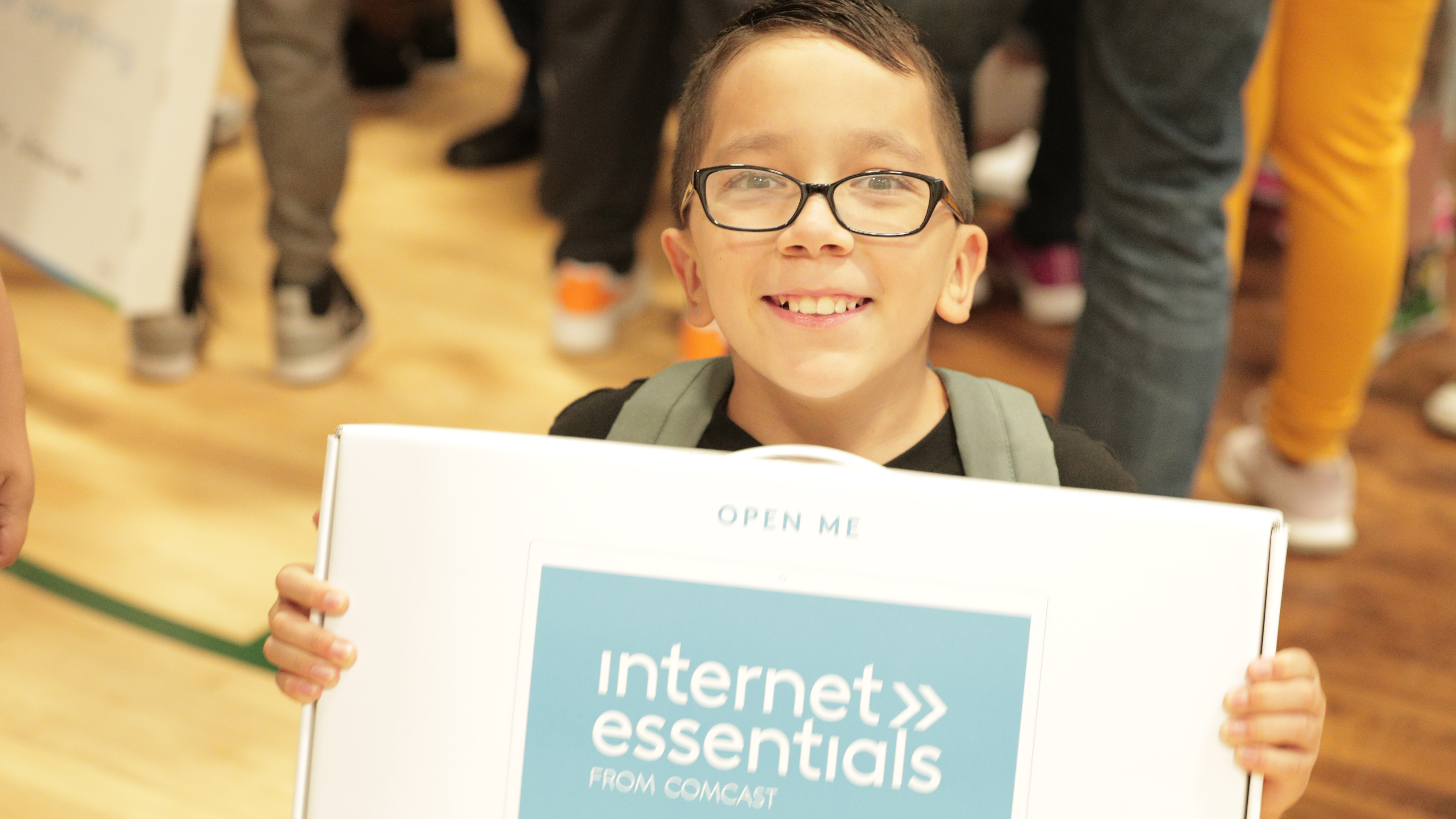 A child holds up their new Internet Essentials laptop at an event in Denver.