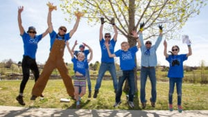 Comcast Cares Day volunteers jump in the air.