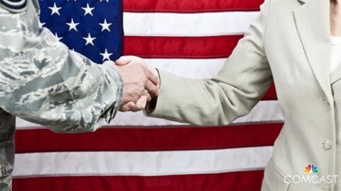 Two people shake hands in front of an American flag.