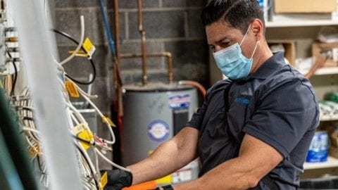 An employee working wearing a mask.